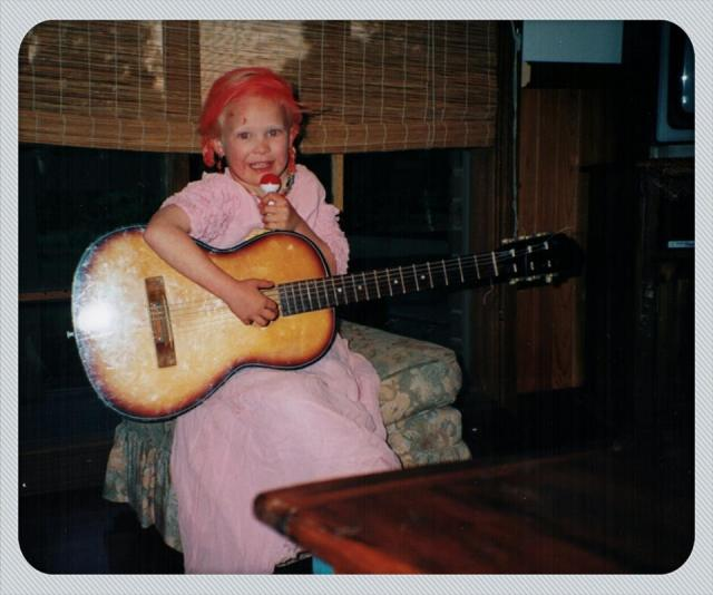 A photo that my mother took of me when I was 5 years old with red spray-painted hair, a 1980s puffy pink dress and a nylon strong guitar.