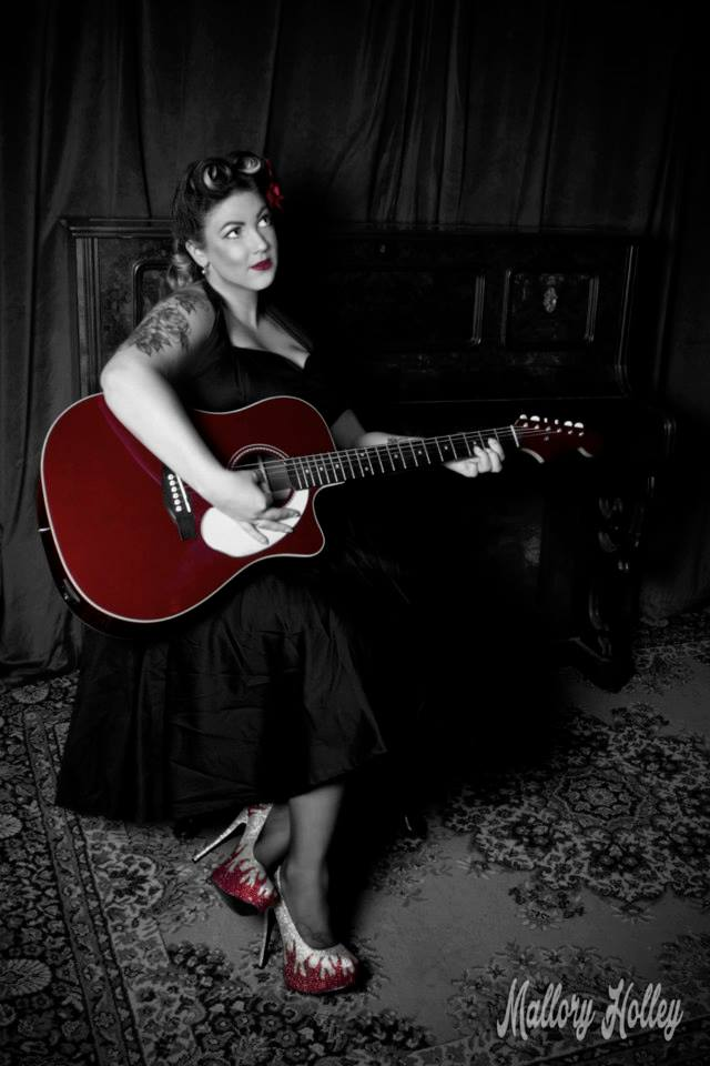 Pinup beauty Miss Laura playing fender guitar